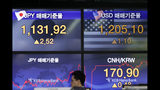 A currency trader walks by screens showing the foreign exchange rates at the foreign exchange dealing room in Seoul, South Korea, Friday, Aug. 23, 2019. Asian stock markets were mixed on Friday after Wall Street declined ahead of a closely watched speech by the U.S. Federal Reserve chairman. (AP Photo/Lee Jin-man)