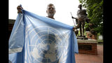 In this Wednesday, Aug. 21, 2019 photo, Lewis Randa, of Duxbury, Mass., displays a United Nations flag while standing near a bronze statue of Indian independence leader Mahatma Gandhi, behind right, at the Pacifist Memorial, in Sherborn, Mass. Randa says in mid-August of 2019 he removed the flag because owners of a condo association, who now own the land on which the Pacifist Memorial is located, argue it violates their property agreement. Randa founded the memorial in 1994. (AP Photo/Steven Senne)