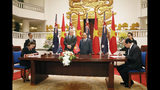 Australian Prime Minister Scott Morrison, center left, and his Vietnamese counterpart Nguyen Xuan Phuc, center right, witness a signing ceremony at the Government Office in Hanoi, Friday, Aug. 23, 2019. Morrison is on an official visit to Vietnam from Aug. 22-24, 2019. (AP Photo/Duc Thanh, Pool)