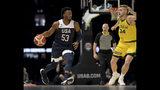 El estadounidense Donovan Mitchel es defendido por el australiano Jock Landale durante el juego de exhibición del sábado 24 de agosto de 2019, en Melbourne. (AP Foto/Andy Brownbill)