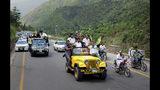 Periodistas hacen señales de victoria mientras participan en una marcha hacia la Línea de Control, que divide la región del Himalaya, en Chinari, una pequeña zona de la Cachemira de control paquistaní, el sábado 24 de agosto de 2019. (Foto AP/M.D. Mughal)