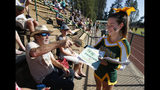 Randall Ward buys a Paradise High School football game program from cheerleader Averie Greenwald at their game against Williams, in Paradise, Calif., Friday, Aug. 23, 2019. This is the first game for the school since a wildfire in November killed multiple people and destroyed nearly 19,000 buildings, including the homes of most of the Paradise players. (AP Photo/Rich Pedroncelli)