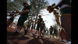 The Paradise junior varsity football team walks past cheerleaders and on to the field for their high school football game against Williams, in Paradise, Calif., Friday, Aug. 23, 2019. This is the first game for the school since a wildfire killed 86 and destroyed nearly 19,000 buildings, including the homes of most of the players. The varsity will play Williams following the junior varsity game. (AP Photo/Rich Pedroncelli)