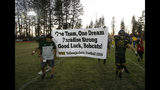 Paradise High School football team members carry a banner presented to them from the visiting Williams High School team before their game in Paradise, Calif., Friday, Aug. 23, 2019. This was the first game for the school since a wildfire last year that killed dozens and destroyed nearly 19,000 buildings including the homes of most of the players. Paradise won 42-0. (AP Photo/Rich Pedroncelli)