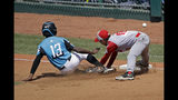 Curacao's Jurdrick Profar (13) slides into third base as the ball gets away from Japan's Yuto Misaki (18) and scored on the play in the first inning of the International Championship baseball game at the Little League World Series tournament in South Williamsport, Pa., Saturday, Aug. 24, 2019. (AP Photo/Tom E. Puskar)