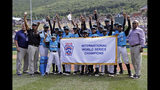 Members of the Curacao Little League team pose with the championship banner after beating Japan 5-4 in the International Championship baseball game at the Little League World Series tournament in South Williamsport, Pa., Saturday, Aug. 24, 2019. (AP Photo/Tom E. Puskar)