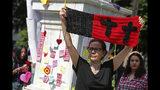 Mónica Ortega levanta un tejido con cruces negras durante un memorial para las mujeres asesinadas en el parque Alameda en Ciudad de México, el sábado 24 de agosto de 2019. (AP Foto/Ginnette Riquelme)