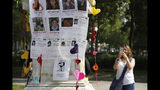 Una mujer toma una fotografía de un pedestal cubierto con imágenes de víctimas durante un memorial para las mujeres asesinadas en el parque Alameda en Ciudad de México, el sábado 24 de agosto de 2019. (AP Foto/Ginnette Riquelme)