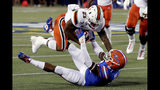 Miami running back Cam'Ron Harris (23) knocks Florida linebacker Ventrell Miller, bottom, to the ground as he is tackled during the first half of an NCAA college football game Saturday, Aug. 24, 2019, in Orlando, Fla. (AP Photo/John Raoux)