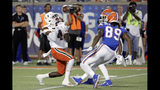 Miami's Jeff Thomas (4) makes a fair catch in front of Florida's Tyrie Cleveland (89) and C.J. McWilliams, back, during the first half of an NCAA college football game Saturday, Aug. 24, 2019, in Orlando, Fla. (AP Photo/John Raoux)