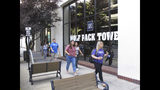 This photo taken Thursday, Aug. 22, 2019 in downtown Reno, Nev., shows University of Nevada, Reno students walking past a Circus Circus casino-hotel tower that has been renamed Wolf Pack Tower. It will house about 1,300 UNR students for the coming school year after a July gas explosion shut down the two largest dorms on the main campus a half-mile away. (AP Photo/Scott Sonner)