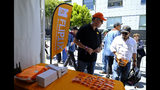 In this photo taken Friday, June 21, 2019, FlipTix CEO Jaime Siegel, left, explains what his company does at the entrance of the Clusterfest comedy event in San Francisco. The company's application lets people who leave a venue early sell their ticket and lets someone who wants the remainder of the ticket buy it. (AP Photo/Eric Risberg)