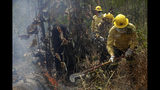 Firefighters work to put out fires in the Vila Nova Samuel region, along the road to the National Forest of Jacunda, near to the city of Porto Velho, Rondonia state, part of Brazil's Amazon, Sunday, Aug. 25, 2019. Leaders of the Group of Seven nations said Sunday they were preparing to help Brazil fight the fires burning across the Amazon rainforest and repair the damage even as tens of thousands of soldiers were being deployed to fight the blazes that have caused global alarm. (AP Photo/Eraldo Peres)