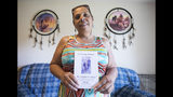 Katina Locklear's sister, Jane Jacobs, poses for a portrait in her Wilmington, N.C., home with the program from her sister's December 2018 funeral. Locklear, a Tuscarora woman, was a 46-year-old mother of four and grandmother of two. She was raped and murdered in a patch of woods in Pembroke, N.C., after a dispute over missing money, which was later found elsewhere. Jacobs now advocates for justice for her sister and other missing and murdered indigenous women across North America. (Julia Wall/The News & Observer via AP)
