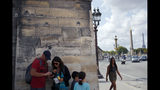 Tourists stand under bullet holes, which remain from the fight for the liberation of Paris, mid August 1944, along the wall of the Tuileries Garden at the place de la Concorde in Paris, Tuesday, Aug. 20, 2019. Paris suffered no major damage during the fighting, though official edifices still bear the bullet holes of fighting. (AP Photo/Francois Mori)