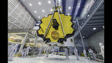 FILE - In this April 13, 2017 file photo provided by NASA, technicians lift the mirror of the James Webb Space Telescope using a crane at the Goddard Space Flight Center in Greenbelt, Md. The telescope's 18-segmented gold mirror is specially designed to capture infrared light from the first galaxies that formed in the early universe. (Laura Betz/NASA via AP, File)