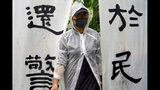 """A woman wears a raincoat stands next to banners that read """"The duty fulfilled by the police belongs to the people"""" as people take part in a rally to support the Hong Kong's Police at Edinburgh Place in Hong Kong, Sunday, Aug. 25, 2019. (AP Photo/Vincent Yu)"""