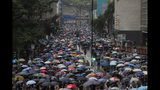 Thousands of demonstrators march in the rain in Hong Kong, Sunday, Aug. 25, 2019. Umbrella-carrying protesters took to the streets in the rain Sunday in Hong Kong's latest pro-democracy demonstration, one day after the return of clashes with police who used tear gas to disperse them. (AP Photo/Kin Cheung)