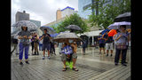 """People carrying umbrellas in the rain hold placards reads """"The duty fulfill by the police belong to the people"""" as they take part in a rally to support the Hong Kong's Police at Edinburgh Place in Hong Kong, Sunday, Aug. 25, 2019. (AP Photo/Vincent Yu)"""