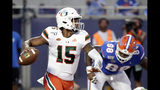Miami quarterback Jarren Williams (15) looks for a receiver as he is pressured by Florida defensive lineman Adam Shuler (88) during the first half of an NCAA college football game Saturday, Aug. 24, 2019, in Orlando, Fla. (AP Photo/John Raoux)
