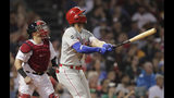 Philadelphia Phillies right fielder Bryce Harper, right, watches the flight of his two run home run in the fifth inning during a baseball game against the Boston Red Sox at Fenway Park in Boston, Wednesday, Aug. 21, 2019. At left is Boston Red Sox catcher Christian Vazquez. (AP Photo/Charles Krupa)