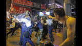 A man throws a brick to policemen on a street during a protest in Hong Kong, Sunday, Aug. 25, 2019. Hong Kong police have rolled out water cannon trucks for the first time in this summer's pro-democracy protests. The two trucks moved forward with riot officers Sunday evening as they pushed protesters back along a street in the outlying Tsuen Wan district. (AP Photo/Kin Cheung)