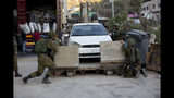 Israeli forces confiscate a car near the area of an attack, west of the West Bank city of Ramallah, Sunday, Aug. 25. 2019. An explosion Friday near a West Bank settlement that Israel said was a Palestinian attack killed a 17-year-old Israeli girl and wounded her brother and father, Israeli authorities said. (AP Photo/Majdi Mohammed)