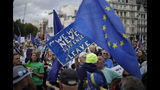 """A leave supporter, left holding sign, tussles with a remain supporter, right holding EU flag, during a demonstration on Parliament Square in London, Wednesday, Sept. 4, 2019. With Britain's prime minister weakened by a major defeat in Parliament, defiant lawmakers were moving Wednesday to bar Boris Johnson from pursuing a """"no-deal"""" departure from the European Union. (AP Photo/Matt Dunham)"""