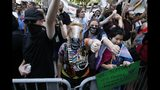Counterprotesters, including one wearing a horse mask, line the route of the Straight Pride Parade in Boston, Saturday, Aug. 31, 2019. (AP Photo/Michael Dwyer)
