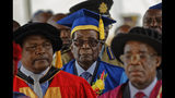 FILE - In this Friday, Nov. 17, 2017 file photo Zimbabwe's President Robert Mugabe, center, arrives to preside over a student graduation ceremony at Zimbabwe Open University on the outskirts of Harare, Zimbabwe. On Friday, Sept. 6, 2019, Zimbabwe President Emmerson Mnangagwa said his predecessor Robert Mugabe, age 95, has died. (AP Photo/Ben Curtis, File)