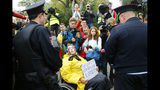 """In this Saturday, Aug. 17, 2019 photo, A wheelchair bound woman activist surrounded by journalists holds a poster reading """"The Constitution breakers to be brought to justice!"""" as she talks to police officers during a protest in the center of Moscow, Russia, A seemingly second-tier local election has evolved into a major challenge to Russia's President Vladimir Putin, triggering the biggest protests against his rule in seven years and causing divisions among his top lieutenants. (AP Photo/Alexander Zemlianichenko, File)"""