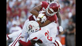Oklahoma running back Kennedy Brooks, top, fights through South Dakota defender Phillip Powell, bottom, for a touchdown in the second quarter of an NCAA college football game Saturday, Sept. 7, 2019, in Norman, Okla. (AP Photo/Sue Ogrocki)
