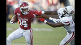 Oklahoma wide receiver Charleston Rambo (14) fights off a tackle from South Dakota defender Cori Fant Jr., right, in the first quarter of an NCAA college football game Saturday, Sept. 7, 2019, in Norman, Okla. (AP Photo/Sue Ogrocki)
