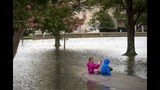 Azalea Sowers, 7, and Isak Asmundsson, 7, sit in the middle of Mowbray Arch in Norfolk, Va., which flooded as a result of the storms caused by Hurricane Dorian on Friday, Sept. 6, 2019. (Sarah Holm/The Virginian-Pilot via AP)