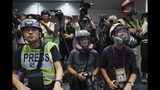 In a sign of protest against the police using force against the media, press photographers wear protective gear during a police media conference in Hong Kong, on Monday, Sept. 9, 2019. Hong Kong's government agreed last week to withdraw an extradition bill that sparked a summer of protests, but demonstrators want other demands to be met, including direct elections of city leaders and an independent inquiry into police actions. (AP Photo/Kin Cheung)