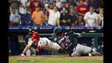 Philadelphia Phillies' Scott Kingery, left, scores past Atlanta Braves catcher Francisco Cervelli after hitting an inside the park home run during the third inning of a baseball game, Tuesday, Sept. 10, 2019, in Philadelphia. (AP Photo/Matt Slocum)