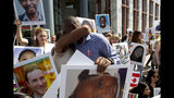 Paul Njoroge of Kenya, holds the picture of his daughter as he gets a hug during a vigil on the six-month anniversary of the crash of a Boeing 737 Max 8, killing 157 people, in Ethiopia on March 10, which has resulted in the grounding hundreds of the planes worldwide, outside of the Department of Transportation, Tuesday, Sept. 10, 2019 in Washington. (AP Photo/Jose Luis Magana)