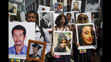Beza Alemu, left, from Ethiopia, along with other demonstrators, holds pictures of his brother Mulusew Alemu, who died in the plane crash, during a vigil on the six-month anniversary of the crash of a Boeing 737 Max 8, killing 157 people, in Ethiopia on March 10, which has resulted in the grounding hundreds of the planes worldwide, outside of the Department of Transportation, Tuesday, Sept. 10, 2019 in Washington. (AP Photo/Jose Luis Magana)