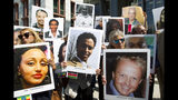 Demonstrators hold pictures of plane crash victims during a vigil on the six-month anniversary of the crash of a Boeing 737 Max 8, killing 157 people in Ethiopia on March 10, which has resulted in the grounding hundreds of the planes worldwide, outside of the Department of Transportation, Tuesday, Sept. 10, 2019 in Washington. (AP Photo/Jose Luis Magana)