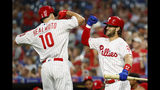 Philadelphia Phillies' J.T. Realmuto, left, and Bryce Harper celebrate after a home run by Realmuto during the first inning of a baseball game against the Atlanta Braves, Tuesday, Sept. 10, 2019, in Philadelphia. (AP Photo/Matt Slocum)