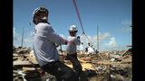 Miembros del equipo de bomberos Task Force 8, de Gainesville, Florida, ayudan a sacar un cuerpo de entre los escombros, una semana después de que el huracán Dorian golpeara el vecindario de The Mudd, en la zona de Marsh Harbor de la Isla Ábaco, Bahamas, el lunes 9 de septiembre de 2019. (AP Foto/Gonzalo Gaudenzi)