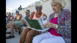 Linda Guthrie, left, and Betty Hughes look at the program during the opening of the new Children's Health Stadium at Prosper ISD on Saturday, Aug. 17, 2019 in Prosper, Texas. Democrats are out to show they're serious about flipping Texas in 2020 by holding Thursday's presidential debate in Houston. Republicans are coming off their worst election in Texas in a generation. Fast-changing suburbs are trending more liberal, and Democrats are counting on more left-leaning voters moving in to turn the state blue. But that transformation may not arrive by 2020, and the GOP is closely watching conservative bastions like the booming Dallas suburbs. (AP Photo/Nathan Hunsinger)