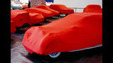 Cars are covered with red sheets ahead of the start of the IAA Auto Show in Frankfurt, Germany, Sunday, Sept. 8, 2019. (AP Photo/Michael Probst)