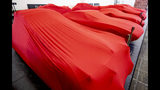 Cars are covered with red blankets at the IAA Auto Show in Frankfurt, Germany, Monday, Sept. 9, 2019. The IAA officially starts with media days on Tuesday and Wednesday. (AP Photo/Michael Probst)