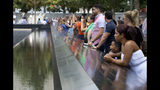 FILE- In this Sept. 9, 2015 file photo, visitors look at the waterfalls at the World Trade Center Memorial in New York. As they have done 17 times before, a crowd of victims' relatives is expected at the site on Wednesday, Sept. 11, 2019 to observe the anniversary the deadliest terror attack on American soil. (AP Photo/Mark Lennihan)