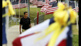 A man visits Memorial Gardens Park in Odessa, Texas, Monday, Sept. 9, 2019, walking by the seven Texas flags that represent the seven killed in a recent shooting in the Odessa and Midland area. (Ben Powell/Odessa American via AP)