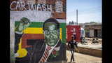 A man walks past a mural of former president Robert Mugabe, in the low income neighbourhood of Mbare, known to have many supporters of Mugabe's ZANU-PF party, in the capital Harare, Zimbabwe Monday, Sept. 9, 2019. Mugabe, who enjoyed strong backing from Zimbabwe's people after taking over in 1980, but whose support waned following decades of repression, economic mismanagement and allegations of election-rigging, is expected to be buried on Sunday, state media reported. (AP Photo/Ben Curtis)