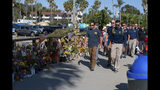 """FBI agents walk past a memorial for the victims of the Conception dive boat on the Santa Barbara Harbor, as authorities issue a search warrant for the Truth Aquatics' offices in Santa Barbara, Calif., Sunday, Sept. 8, 2019. The office was ringed in red """"crime scene"""" tape as more than a dozen agents took photos and carried out boxes. Thirty-four people died when the Conception burned and sank before dawn on Sept. 2. They were sleeping in a cramped bunkroom below the main deck and their escape routes were blocked by fire. (AP Photo/Christian Monterrosa)"""