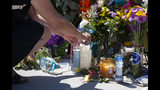 A woman relights a candle placed at a memorial for the victims of the Conception dive boat on the Santa Barbara Harbor on Sunday, Sept. 8, 2019 in Santa Barbara, Calif. Authorities served search warrants Sunday at the Southern California company that owned the scuba diving boat that caught fire and killed 34 people last week. Thirty-four people died when the Conception burned and sank before dawn on Sept. 2. They were sleeping in a cramped bunkroom below the main deck and their escape routes were blocked by fire. (AP Photo/Christian Monterrosa)