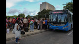 Locals line up to board a public service bus in Havana, Cuba, Wednesday, Sept. 11, 2019. The island nations is facing a diesel fuel shortage but the government said there will be no electricity blackouts. The government blames the recent economic sanctions placed by the U.S. Trump administration for this latest energy crisis. (AP Photo/Ismael Francisco)